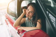 Beautiful young woman buying a car at dealership. Female model sitting Sits in the car interior. Beautiful young women buying a car at dealership. Female model Stock Photos