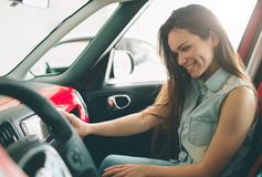 Beautiful young woman buying a car at dealership. Female model sitting Sits in the car interior. Beautiful young women buying a car at dealership. Female model Stock Image
