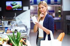 Beautiful young woman buying fresh vegetables and looking shopping list in the market. Shot of beautiful young woman buying fresh vegetables and looking royalty free stock images