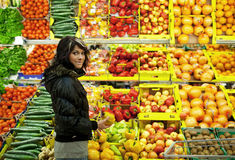 Beautiful young woman buying fruits and vegetables Stock Images