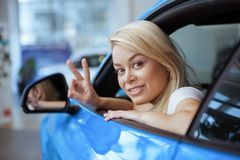 Beautiful young woman buying new car at the dealership stock photos