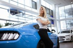 Beautiful young woman buying new car at the dealership stock photo
