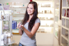 Beautiful young woman buying perfume Royalty Free Stock Photos