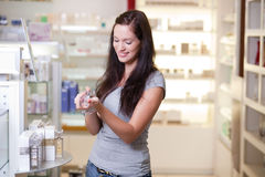 Beautiful young woman buying perfume Royalty Free Stock Photo