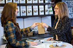 Beautiful young woman buying tea leaves by weight in a organic shop. stock photography