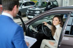Beautiful young woman buys a car in the dealership saloon. Beautiful young women buys a car in the dealership saloon stock images