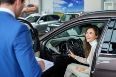 Beautiful young woman buys a car in the dealership saloon. Beautiful young women buys a car in the dealership saloon royalty free stock photography