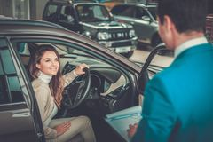 Beautiful young woman buys a car in the dealership saloon. Beautiful young women buys a car in the dealership saloon royalty free stock image