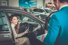 Beautiful young woman buys a car in the dealership saloon. Beautiful young women buys a car in the dealership saloon royalty free stock images