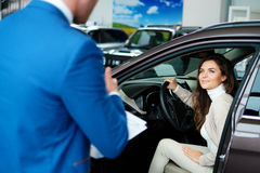 Beautiful young woman buys a car in the dealership saloon Stock Images