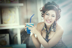 Beautiful young woman in cafe drinking blue soda ice and relaxin Stock Photos