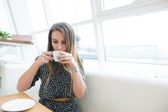 Beautiful young woman in a cafe holding a cup of tea, seen through the window with buildings and lights reflections. Royalty Free Stock Photography