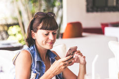 Beautiful young woman in cafe using an application to send an sms message in her smartphone device. Bali. stock images