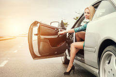 Beautiful young woman came out from the car on road Stock Images
