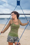 Beautiful young woman in camouflage posing on the beach. Military fashion. Stock Photos