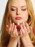 Beautiful young woman with candle look down. Beautiful young woman with candle in glass, look down Stock Images
