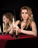 Beautiful young woman with candles near the mirror Stock Photos