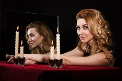 Beautiful young woman with candles near the mirror Royalty Free Stock Photo