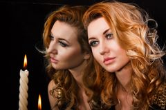Beautiful young woman with candles near the mirror. Over black background Royalty Free Stock Photo