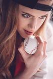 Beautiful young woman in cap holding baseball ball Stock Photography