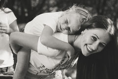 Beautiful young woman carries on her back little sister stock image