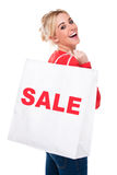 Beautiful Young Woman Carrying Sale Shopping Bag. Beautiful Young Woman Carrying Shopping Bag with Sale Sign Smiling Isolated on White Royalty Free Stock Photography