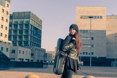 Beautiful young woman carrying saxophone case Stock Photos