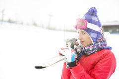 Beautiful young woman carrying skis outdoors Stock Photography
