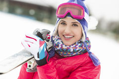 Beautiful young woman carrying skis in snow Stock Image