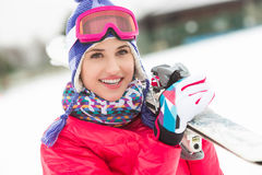 Beautiful young woman carrying skis in snow Stock Photo
