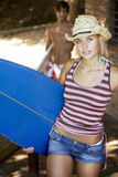 Beautiful Young Woman Carrying Surfboard. Portrait of beautiful young women carrying surfboard with men in background Royalty Free Stock Photo