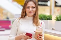 Beautiful young woman in casual clothes drinking lemonade from takeaway plastic cup in cafe, holding smart phone, dressed white. Shirt, has bright red nanicure royalty free stock photography