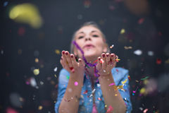 Woman blowing confetti in the air. Beautiful young woman celebrating new year and chrismas party while blowing confetti decorations to camera Royalty Free Stock Images