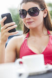 Beautiful Young Woman Cell Phone Texting in Cafe Royalty Free Stock Photography