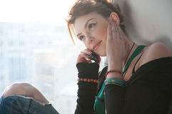 Beautiful young woman with cell phone on window. Stock Photography