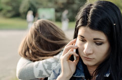 Beautiful young woman chatting on her mobile phone. Beautiful young women chatting on her mobile phone listening conversation concerned expression while her Royalty Free Stock Image