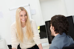 Beautiful young woman chatting to a colleague Royalty Free Stock Photo