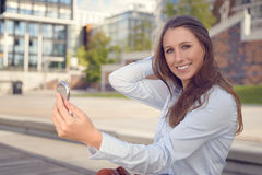 Beautiful young woman checking her appearance Stock Photography