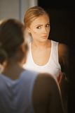 Beautiful young woman checking her face in mirror Stock Photos