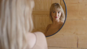 Beautiful young woman checking her face in a mirror. Young woman looking in a mirror and smiling Royalty Free Stock Photos