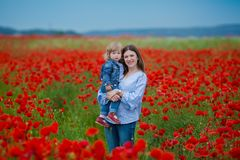 Beautiful young woman with child girl in poppy field. happy family having fun in nature. outdoor portrait in poppies. mother with stock image