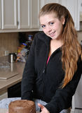 Beautiful young woman with chocolate cake. Beautiful young Caucasian woman relaxing in kitchen smiling in front of chocolate cake Royalty Free Stock Images