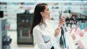 Beautiful young woman chooses mascara in cosmetics store. Concept purchase, shop, buyer stock footage