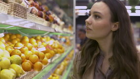 Beautiful young woman chooses oranges and kiwi fruit in a supermarket stock video
