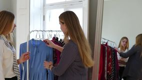 Beautiful young woman is choosing clothes in shop and meeting her female friend. Girls are happy to see each other, they stock video footage