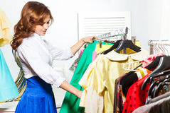Beautiful young woman choosing clothes in shop Stock Images