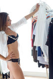 Beautiful young woman choosing clothes to wear at home. Royalty Free Stock Photography