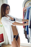 Beautiful young woman choosing clothes to wear at home. Royalty Free Stock Images