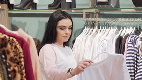 Beautiful young woman choosing t-shirt to buy at the clothing store. Attractive female customer examining clothes on sale at local fashion boutique. Style stock video footage
