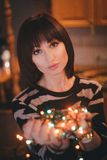 Beautiful young woman with christmas lights. Beautiful young woman holding christmas lights in her hands stock images